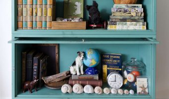 Vintage green metal barrister bookcase filled with vintage items such as books and seashells