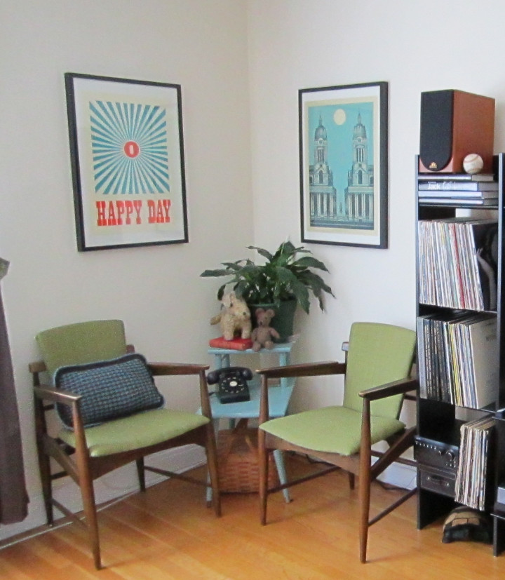 Two vintage chairs with green seats and backs with a blue table and plant and graphic art above them, records on display beside in a shelf