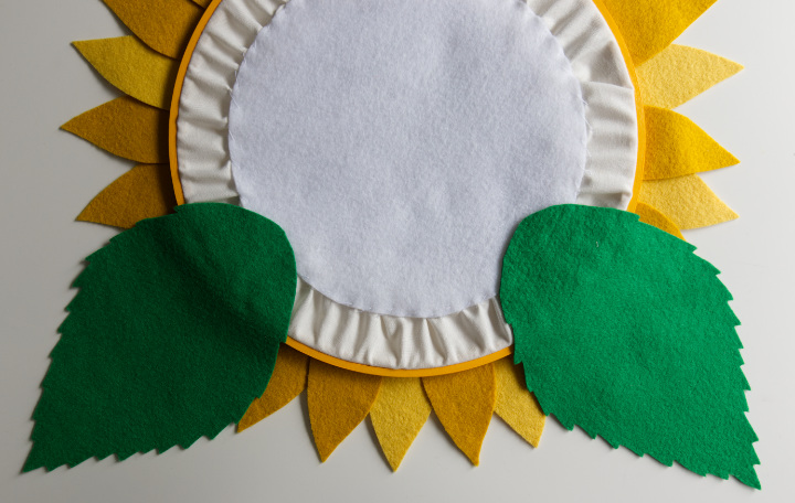 The DIY fall sunflower is shown from the back with the leaves placed at 5 and 7 o'clock on a clock placement and glued where they overlap the hoop