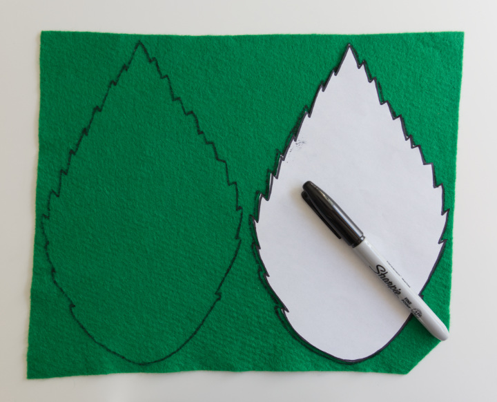 A piece of green felt with a leaf template that has been traced twice in Sharpie.
