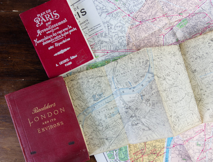 Two small red books of maps of Paris and London with fold out maps spread out