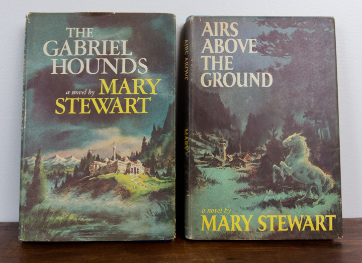 Two hardcovers - The Gabriel Hounds and Airs Above The Ground by Mary Stewart - both have moody dust jackets
