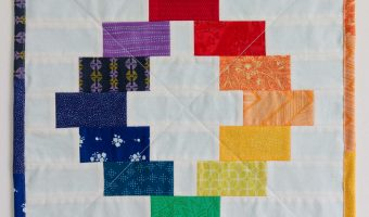 How to Make a Mini Quilt - A mini quilt hangs on the wall - it has a patchwork ring in the shape of the colour wheel with rainbow binding around the edge