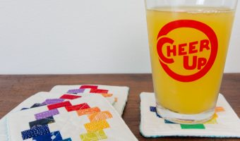 """Three coasters sit in a pile and a small glass of orange juice sits on the fourth, the glass says """"Cheer Up"""" in red graphic writing in a circle."""