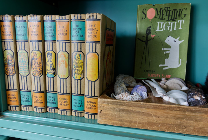 Close up of a set of books - Young Folks Library - orange and turquoise with a wooden tray of seashells