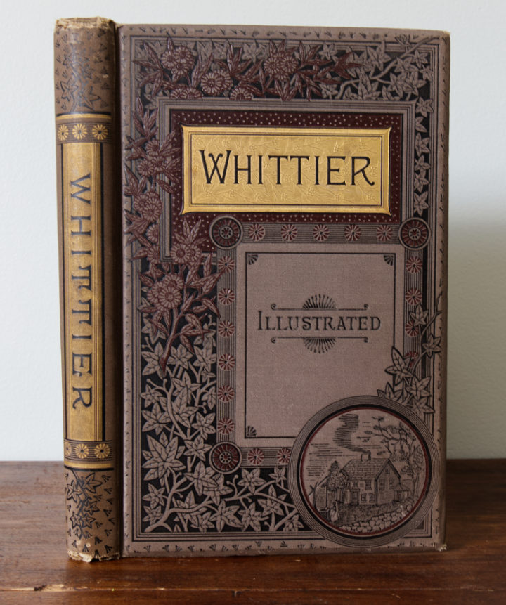 A very ornate Whittier book, dark grey with black scrolling vines and gold