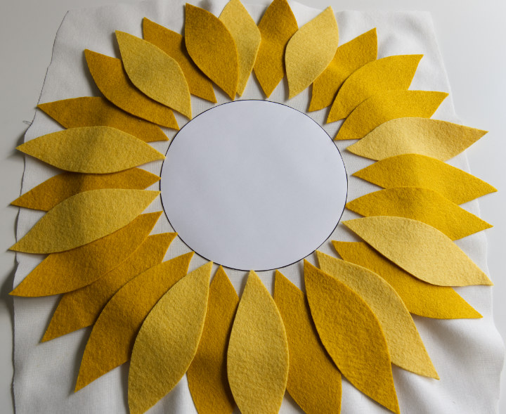 The small circle template is laid in the middle of the hoop and the felt petals have been laid out evenly with points touching the circle and colours distributed evenly