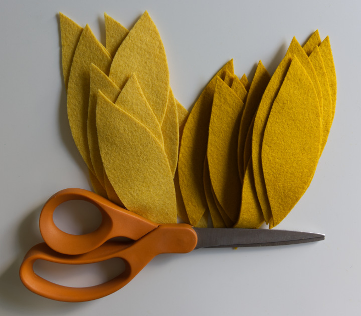 All the yellow petals have been cut from the felt, removing the Sharpie outlines carefully. The piles sit with orange scissors, and will be added to the DIY fall sunflower.
