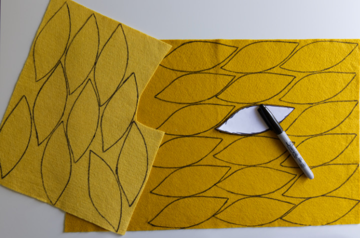 Two shades of yellow felt sheets have 28 petals traced on them from the template with a Sharpie