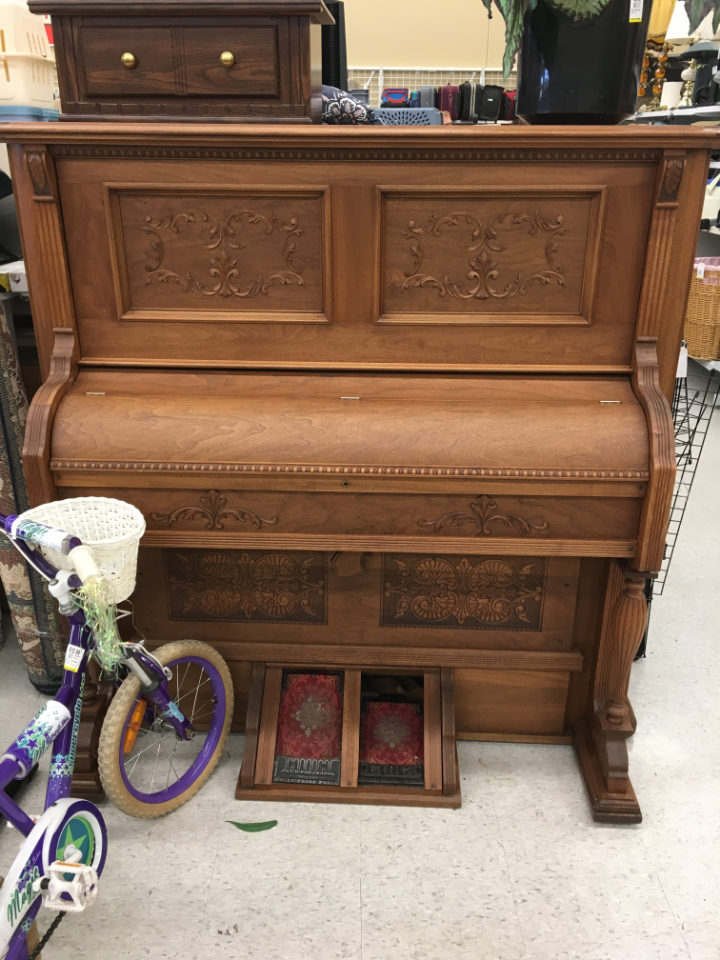 A large piano in a thrift store, the piano has elaborate carvings