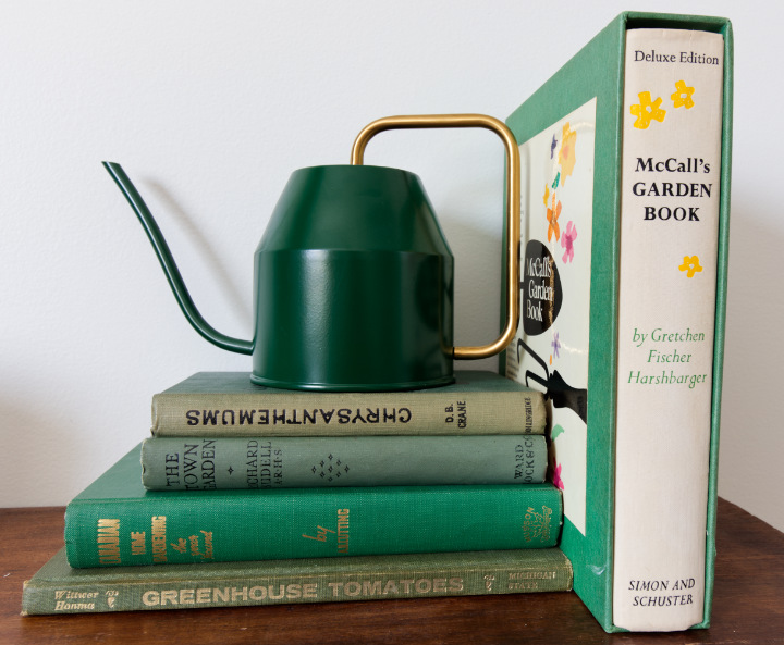 A stack of vintage green gardening books with a small green watering can on top, and a large book in a slipcase beside it