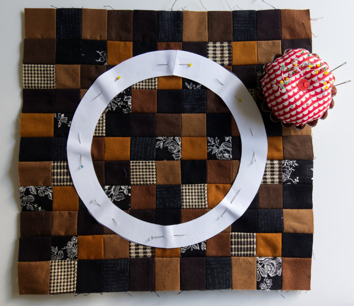 The larger circle template is pinned in the center of the pieced brown and black square
