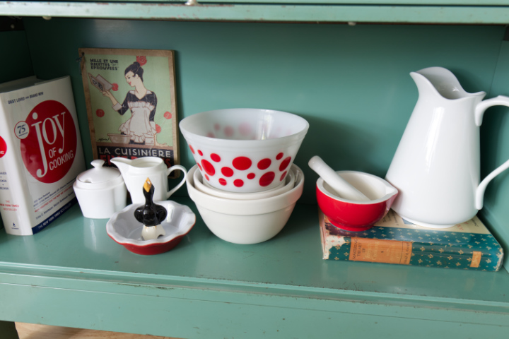 Close up of bottom shelf with polka dot bowl, mortar and pestle, cookbooks and white jug