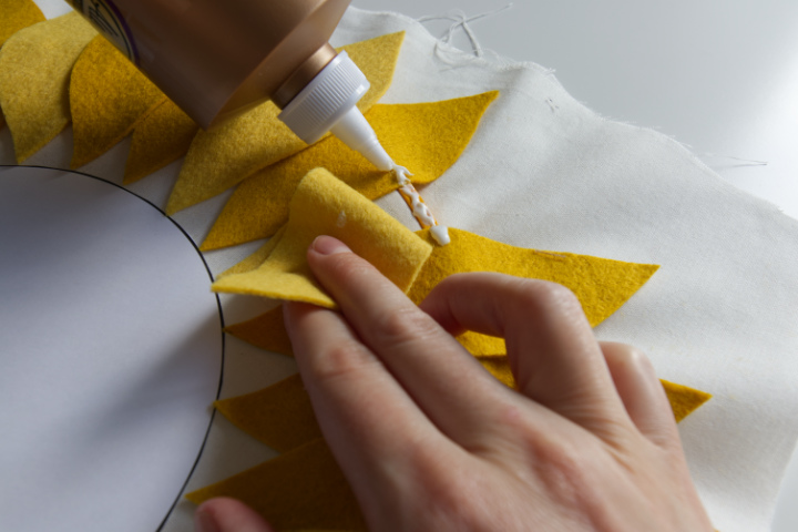 The outside edge of a petal is folded back to place tacky glue on the embroidery hoop