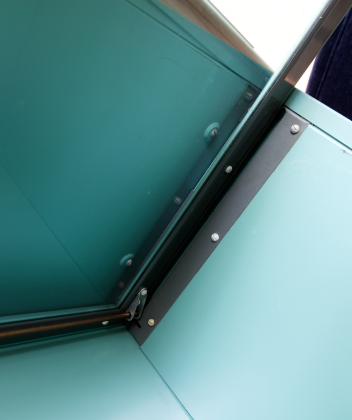View at the underside of the roof of a barrister bookcase section, showing door mechanism and screws that attach the sections together
