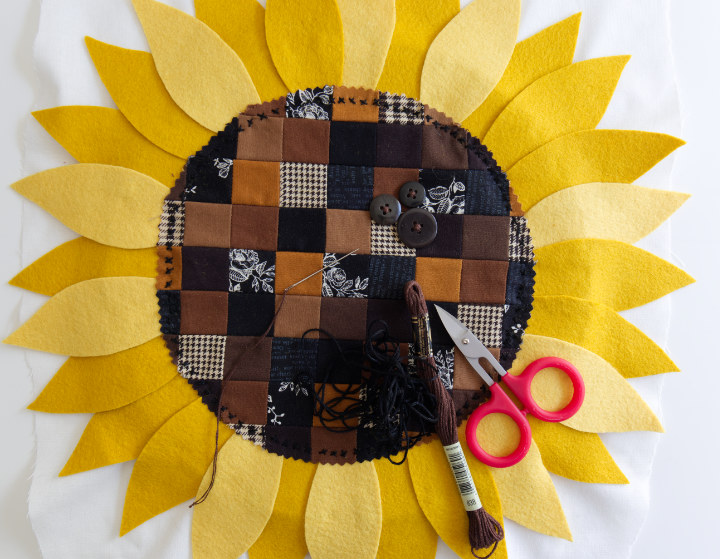The DIY fall sunflower centre has now been stitched to the hoop fabric around the outside edge with little 'X's and 3 brown buttons in different sizes have been sewn on in a cluster.