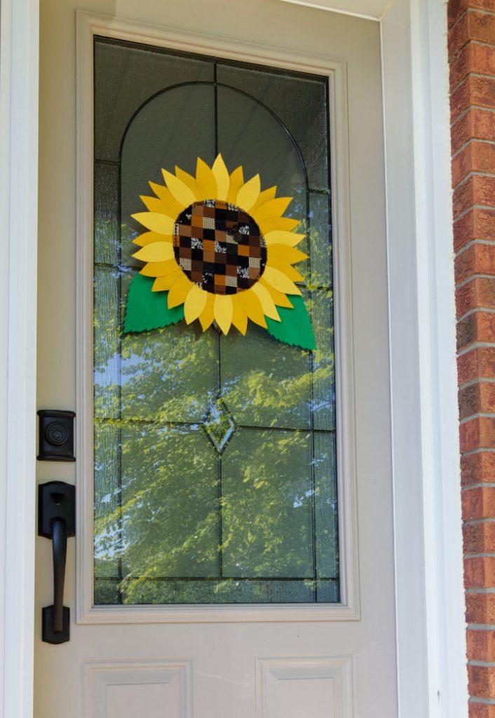 A DIY fall sunflower hanging on a beige front door