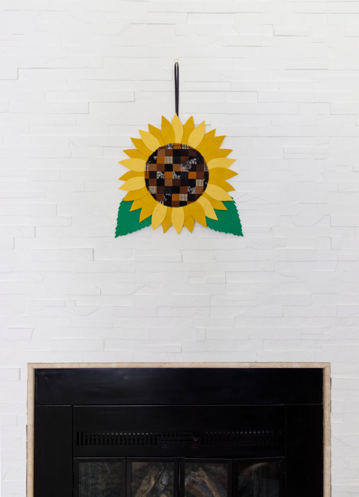 A DIY fall sunflower hangs on a white painted stone fireplace