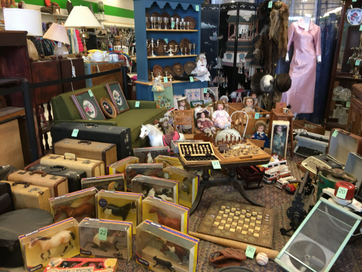 A whole selection of vintage items grouped in a thrift store with numbered tags for auction to raise money - vintage shopping for a cause