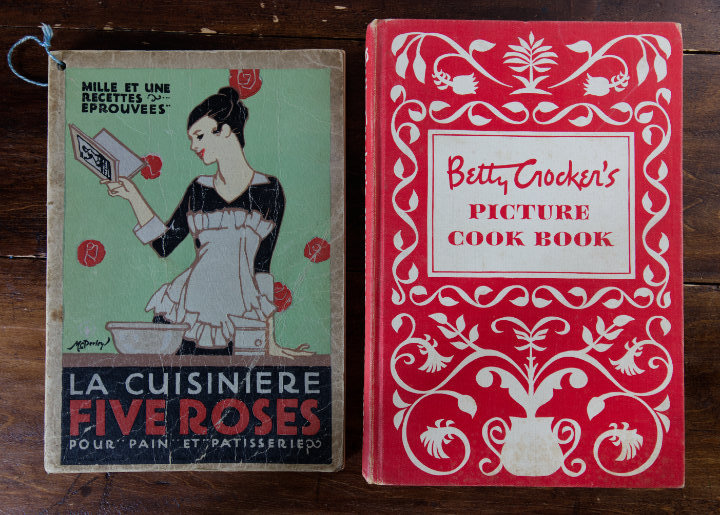 A vintage French Five Roses cookbook with a green cover and an illustration of a woman, and a 1950s Betty Crocker cookbook that's red with white scroll pattern on the front