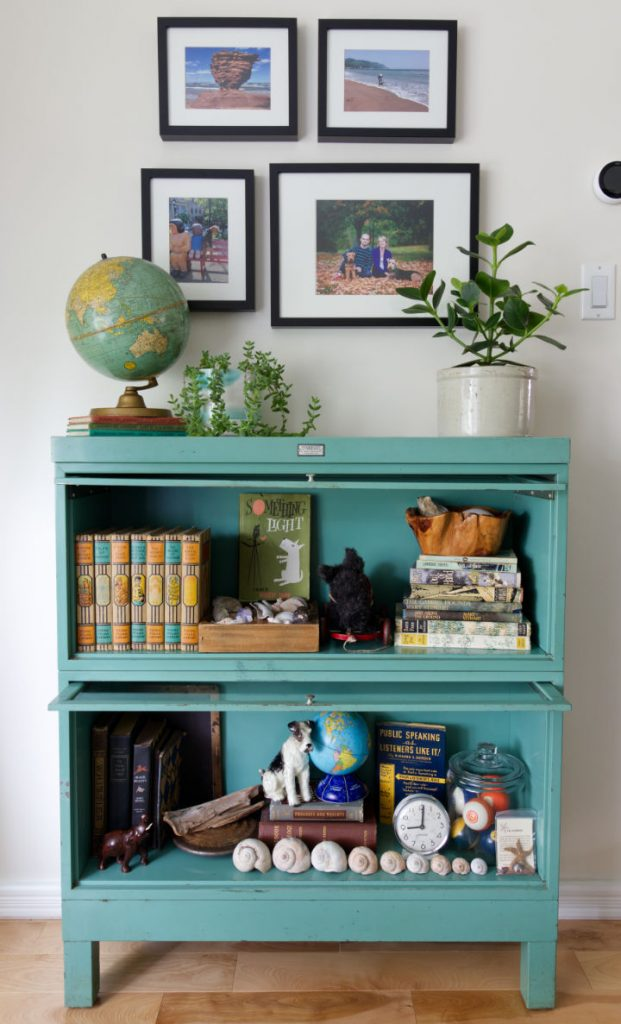 Vintage metal barrister bookcase in blue-green filled with books and decorative items with framed photos above and a globe and a potted plant on top