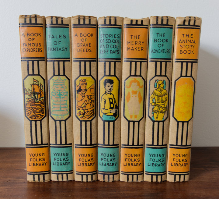 A colourful orange and turquoise set of 7 books from the Young Folks Library, all tales for children, with pictures and graphic lines on the spine