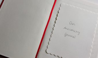 Starting an anniversary journal - The cover page of our red anniversary journal with a red ribbon bookmark