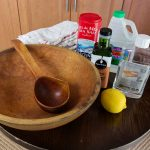 A wood bowl and wood ladle sit on a small table with towels, coarse salt, walnut oil, vinegar, mineral oil and a lemon for cleaning a vintage wood bowl.