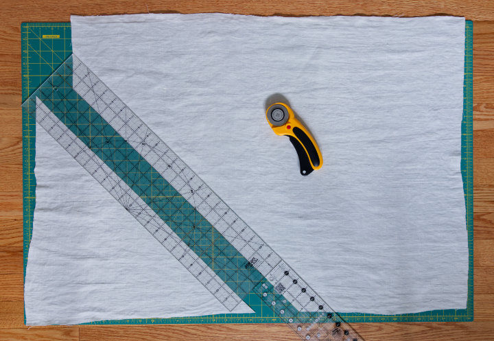 A piece of linen lays on a large cutting mat and cutting 2 inch wide strips at a 45 degree angle for bias piping strips for a piped cushion with zip