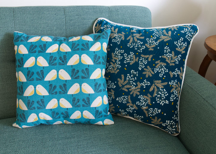 Two finished pillows sit on a green couch, one patterned teal corduroy with white piping and one patterned linen with birds