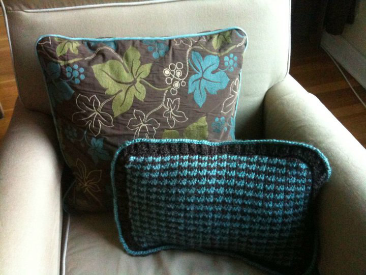 Brown pillow with patterned leaves and turquoise piping with a knitted cushion in a chair - my first piped cushion with zip