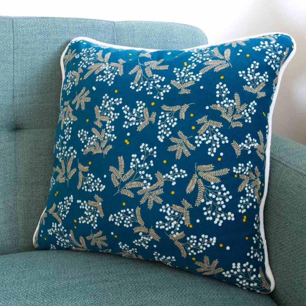 A finished patterned corduroy piped cushion with zip with white piping sits on a green couch.