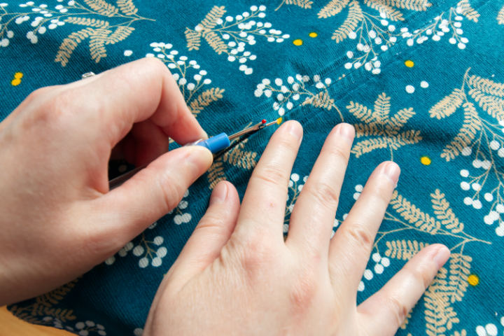 Hands use a seam ripper to cut the basting stitches on the back seam in between the zipper top and bottom