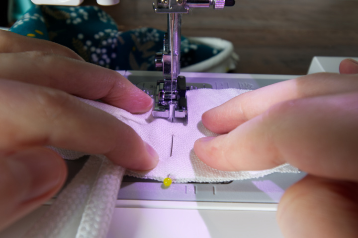 The bias strips marked with a pin are being guided through the sewing machine to stitch in a line where the pin is