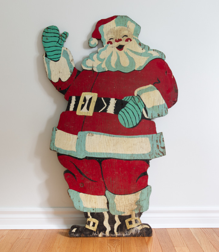 A plywood Santa that has been painted with red and highlights of aqua.