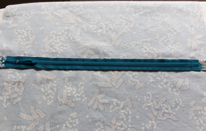 The zipper has been sewn to the seam allowance in a rectangle and backstitched at top and bottom.