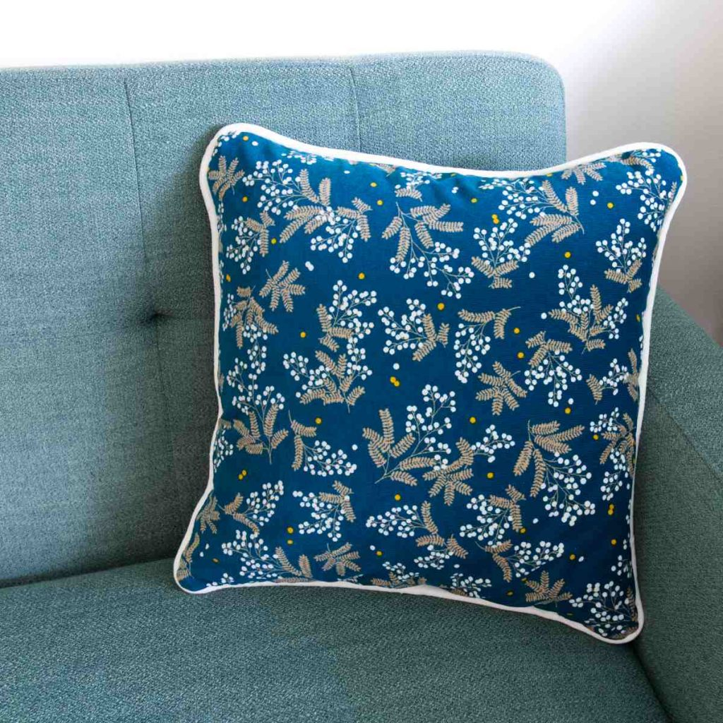 A finished corduroy piped cushion with zip in patterned teal sits on a green couch.