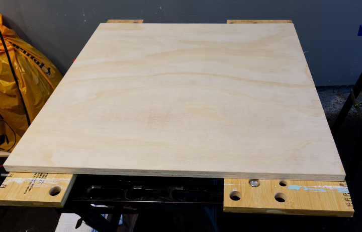 """A bare wood 24"""" square of 3/4"""" plywood sits on a work table"""