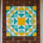 Yellow, Turquoise and Aqua Suburban Barn Quilt hanging on a brick wall