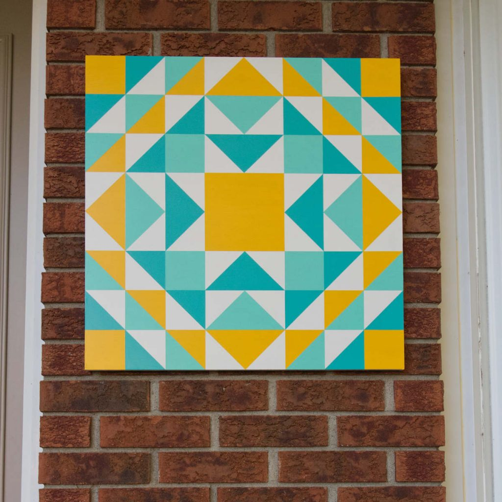 A yellow, turquoise and aqua barn quilt hanging on a brick wall