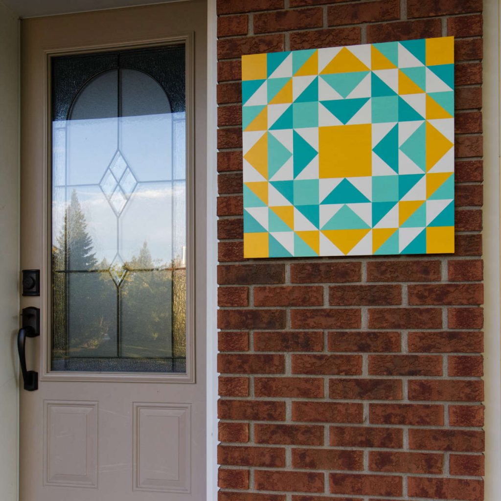 A yellow, turquoise and aqua barn quilt hanging on a brick wall beside a beige front door
