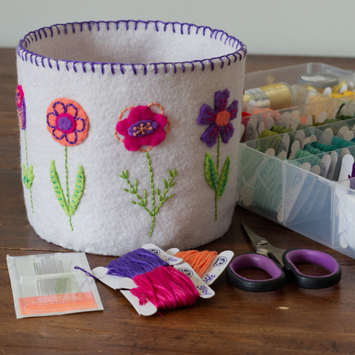 The Blooming Along Basket sits on a table beside embroidery floss, needles and scissors. This basket is white felt with coral, fuschia, and purple flowers