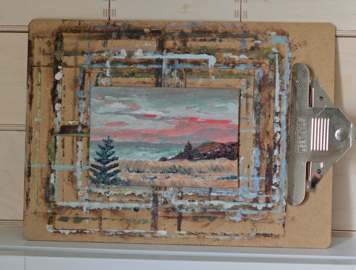 A small painting on a clipboard - dusky sky of moody blues and pinks, along a sandy and reedy shoreline with a hill and an evergreen tree in the foreground