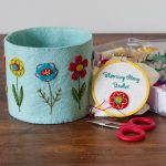 The Blooming Along basket is a embroidered felt basket in aqua felt with gold, red, and turquoise flowers. It's sitting beside a small embroidery hoop in progress that says Blooming Along Basket in embroidery