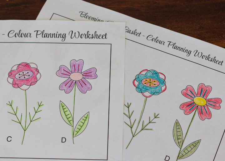 The corners of two printed colour planning worksheets of the flower designs that have been coloured with pencil crayons and can help to plan and choose a felt colour scheme