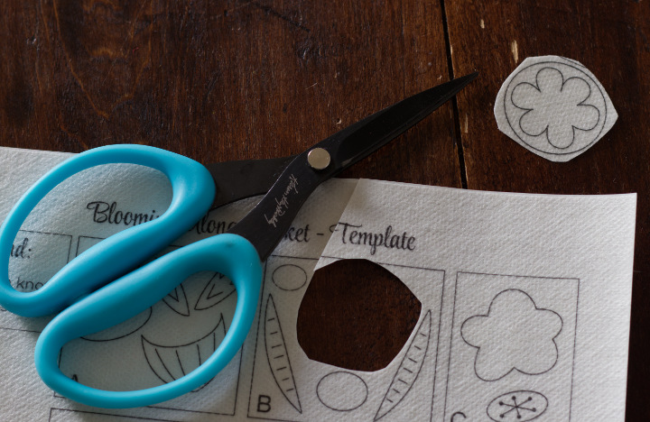 """Aqua """"Perfect Scissors"""" sit beside a printed stabilizer template with a flower shape cut out from it"""