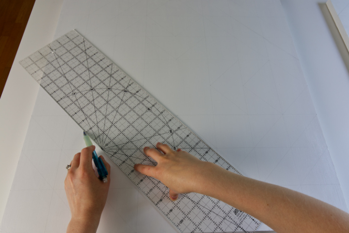 Drawing diagonal lines on the barn quilt with a 24 inch quilting ruler and a pencil