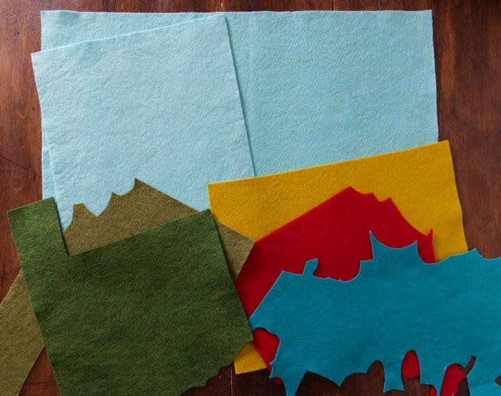 "A 12x18"" sheet and a 9x12"" sheet of aqua felt, plus green felt chunks, gold, red, and turquoise"
