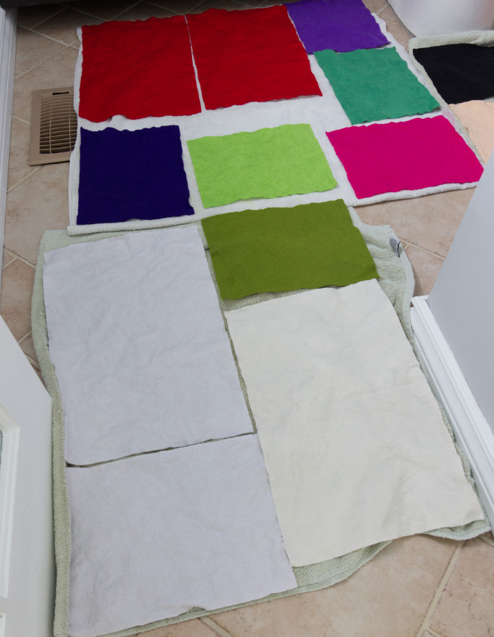 Sheets of wool blend felt drying on towels on a bathroom floor, prepping the materials for felt embroidery