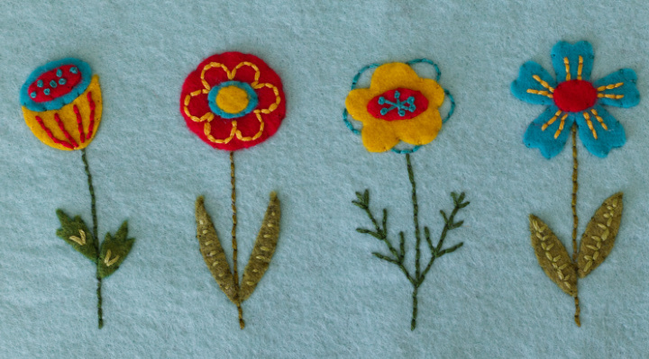 A close-up of 4 different embroidered flowers made with gold, red, turquoise felt on the embroidered felt basket